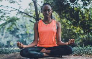 black woman in orange shirt and black leggings meditating outside in wooded area