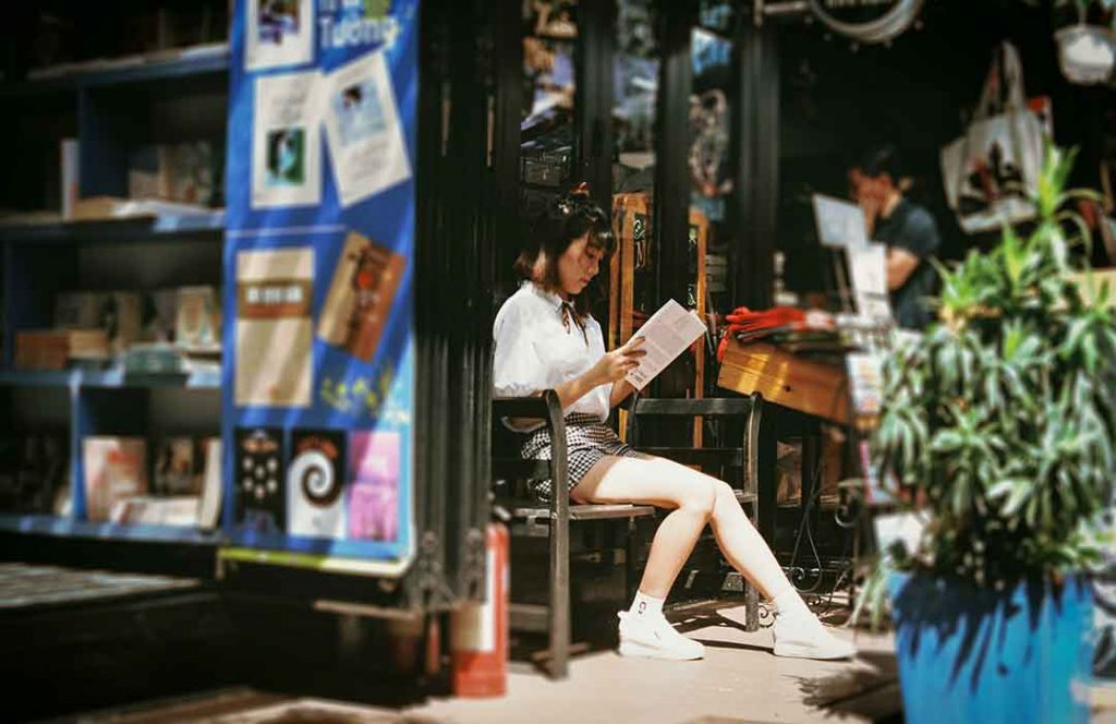 girl in white shirt reaching a book outside on the patio of a bookstore