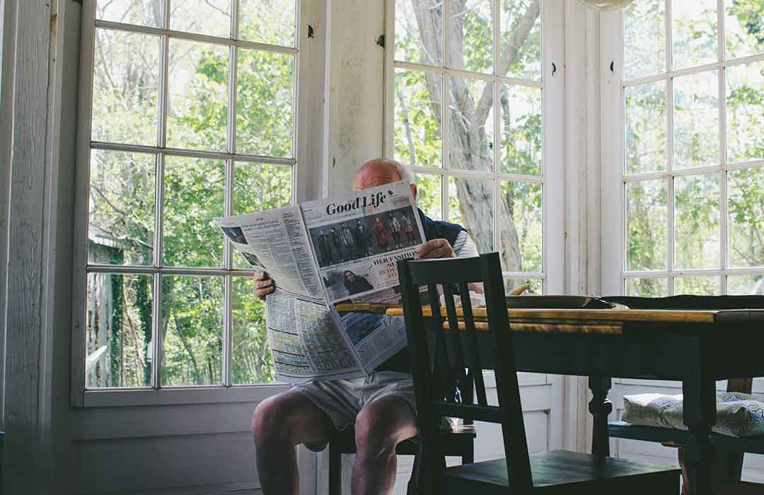elderly man sitting at wood table holding newspaper by windows