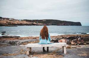 woman with red hair in teal jacket on bench by water