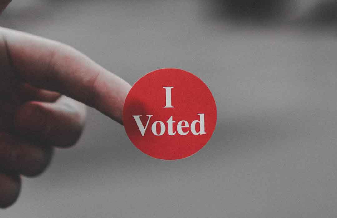 grey background with hand holding a round red sticker that says i voted