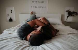 man and woman hugging and laying down on white bed with white posters