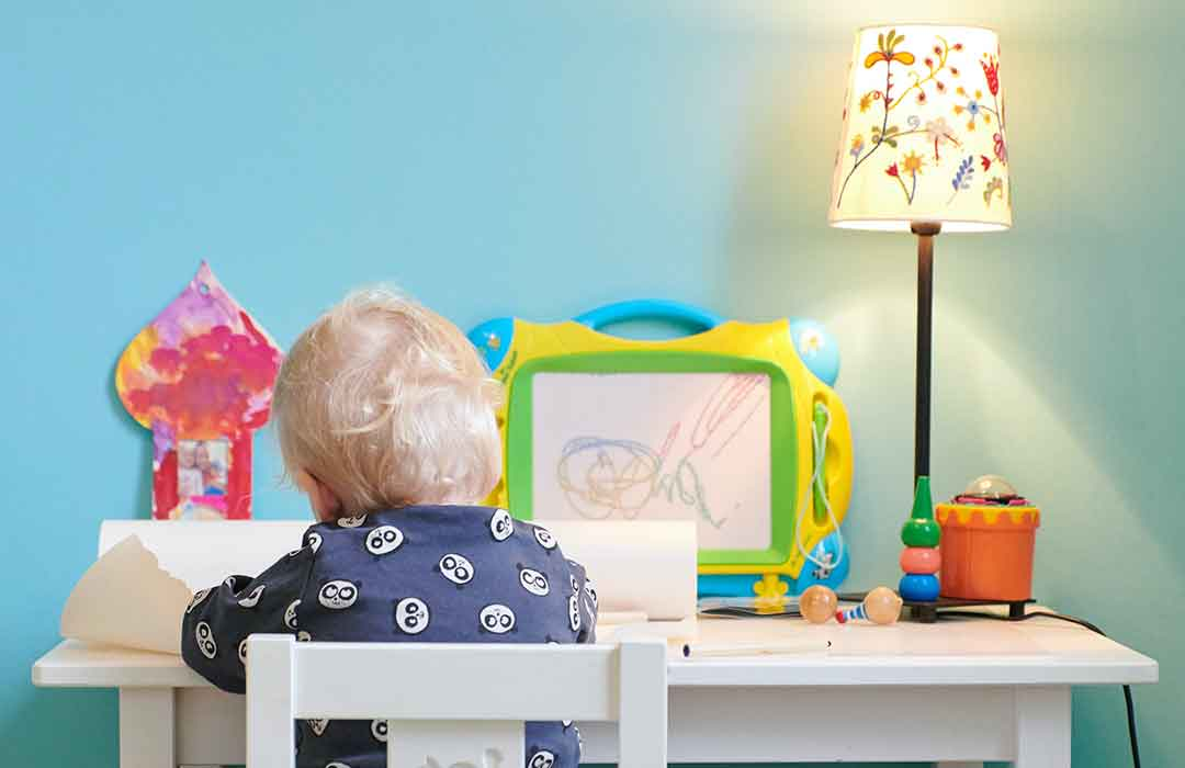 blonde child in blue shirt sitting at teal desk with lamp and toys