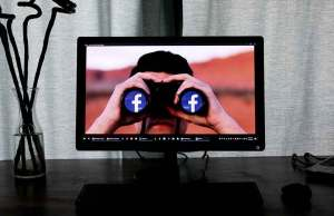 computer screen with man holding binoculars with facebook logo