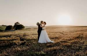 woman in wedding dress holding hands with man in suit outside on hilly landscape