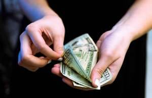 two hands holding money on black background