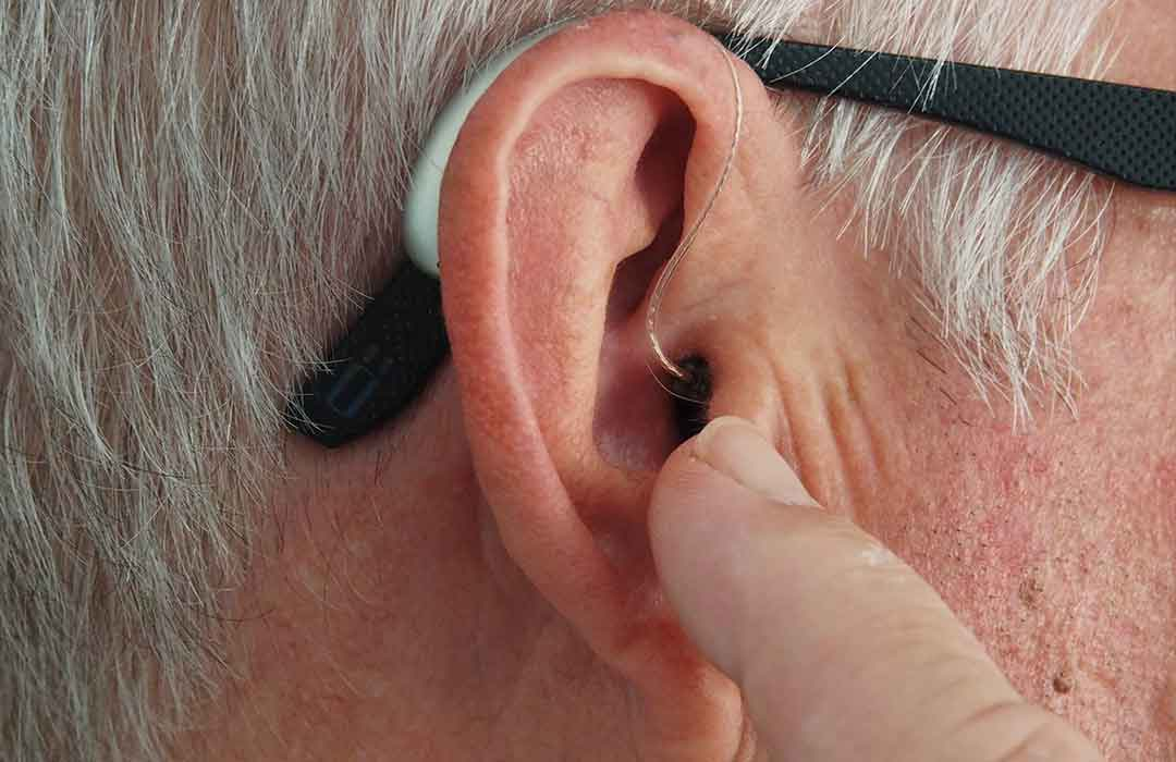 ear with hearing device and black glasses with grey hair