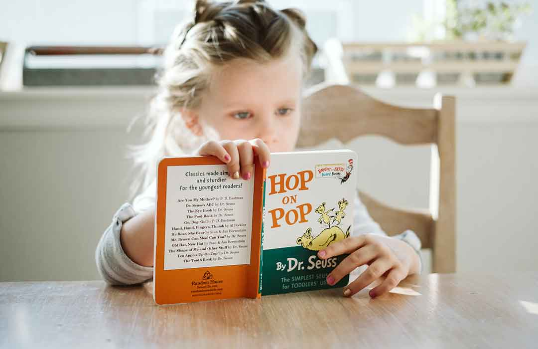 child with braided hair reading hop and pop at a wood table