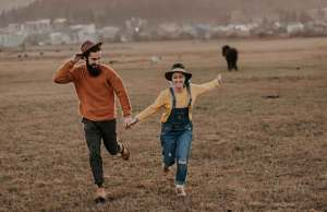 couple in overalls and orange shirt running across grass field