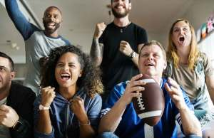 group of men and woman cheering holding a football