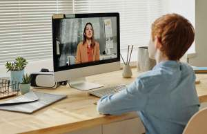 redhead child in blue shirt sitting at desk on computer video chat