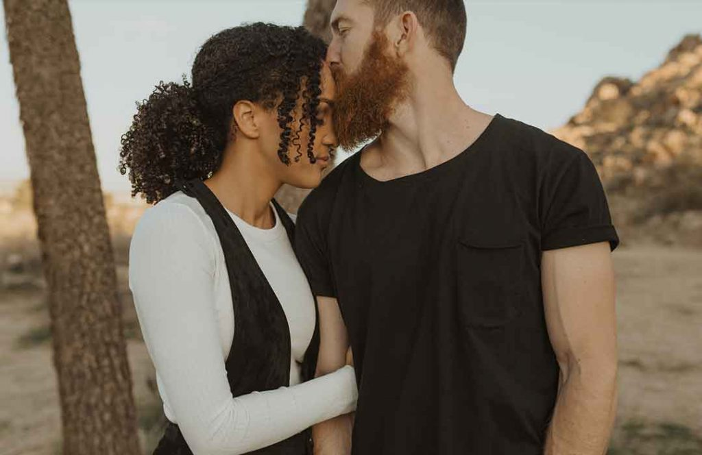 man in black t shirt kissing woman in white shirt and black vest