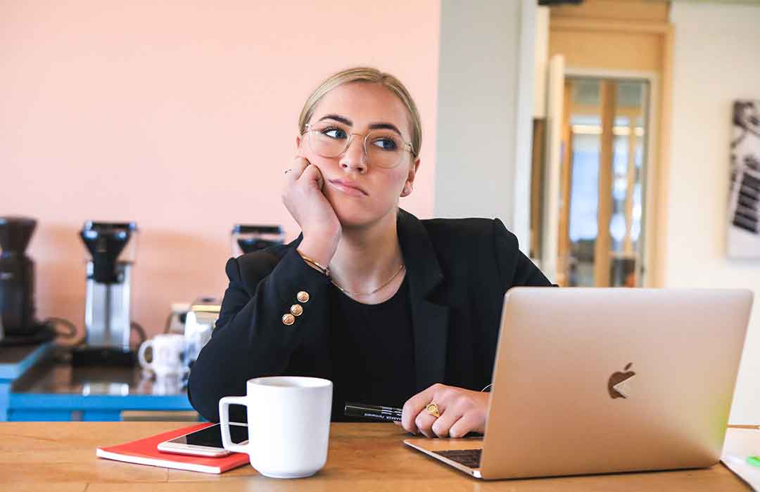 blonde woman in black shirt sitting at desk with Macbook and white coffee mug