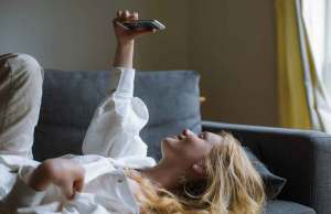 woman in white blouse and khaki pants holding phone on couch