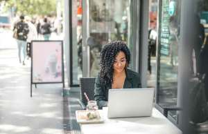 woman with black curly hair in black blazer working outside on laptop