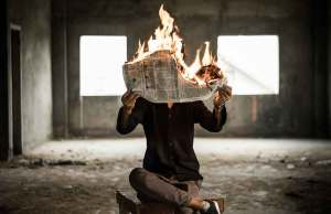 person in black shirt and grey pants sitting in grey room with newspaper on fire