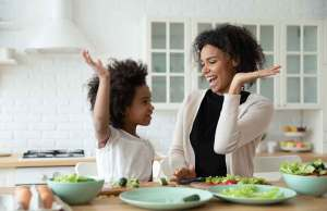 mom and daughter in black and white shirts high fiving at table of food