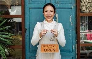 woman in front of teal door holding open sign