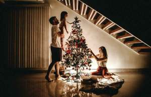 man holding little girl by christmas tree with woman on the floor