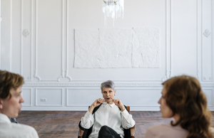 woman in white long sleeve shirt sitting in a chair on wooden floor looking at two individuals