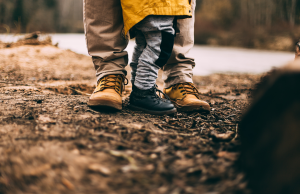 adult and child standing on soil in boots