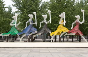five running women wearing different colored dresses holding Olympic torches