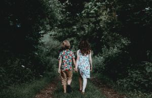 two children holding hands, walking on a path through the woods