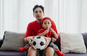 man in red t-shirt sitting on a couch holding a soccer ball and child with a matching shirt