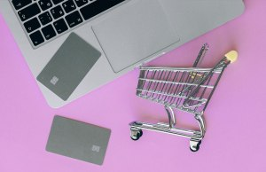 silver shopping cart with silver credit cards and silver macbook computer