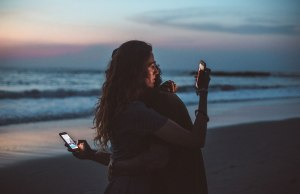 two people hugging and holding cell phones at sunset