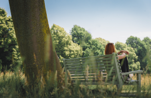 red haired woman city on bench beside tree