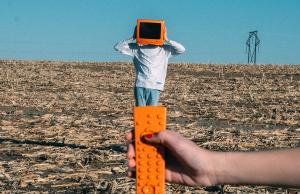 person wearing orange TV helmet with remote in field