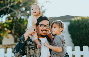 man in white shirt and glasses carrying two kids