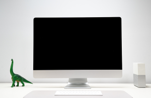 black and white desktop computer with green brontosaurus sitting on desk