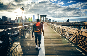 man with backpack walking on bridge in New York City