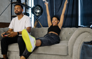 man and woman playing video game while sitting on sofa