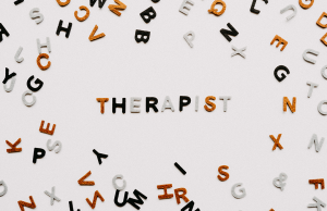 """photo of black, grey, and orange letters spelling """"Therapist"""" with jumbled letters around it"""