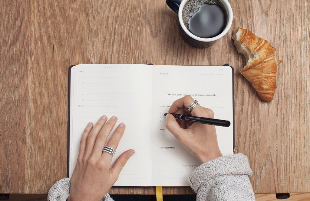 aerial view of person writing in notebook with a cup of coffee and croissant