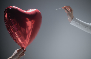 person holding needle towards red hear balloon
