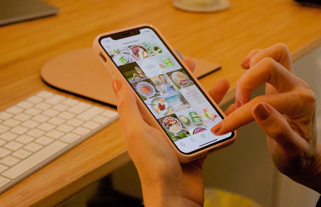 hands holding phone scrolling social media handle