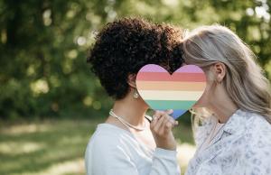 couple kissing behind rainbow heart