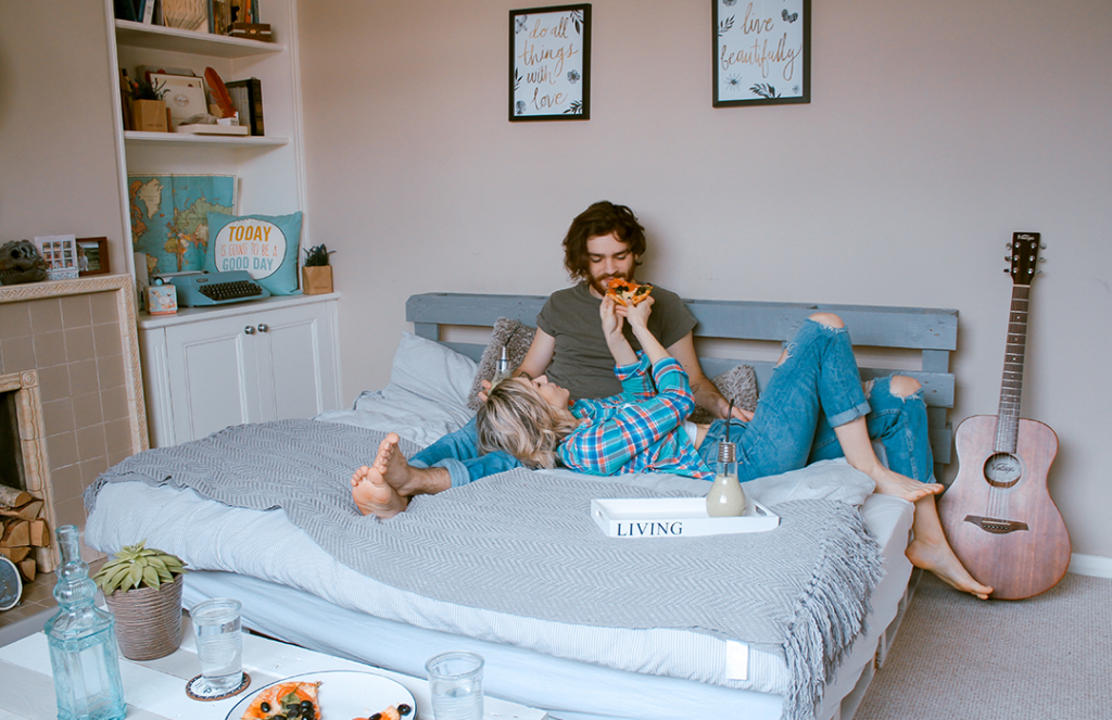 man and woman lying on bed eating pizza