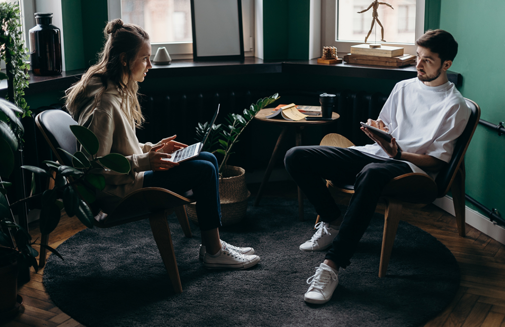 man and woman sitting talking to each other