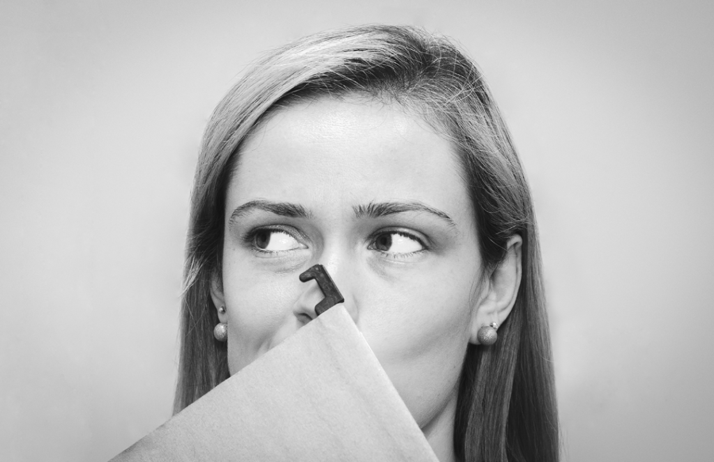 black and white photo of woman covering mouth with file folder