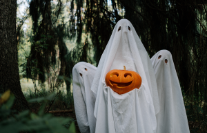 three ghosts holding carved pumpkin