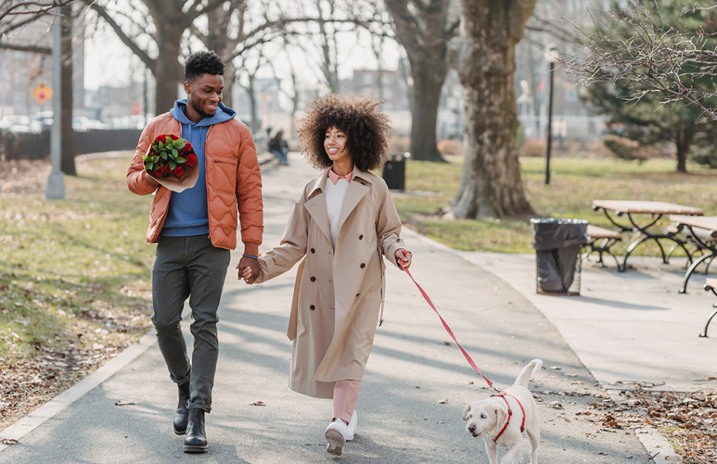 couple walking in park with dog