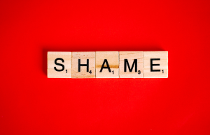 shame spelt out on bright red background
